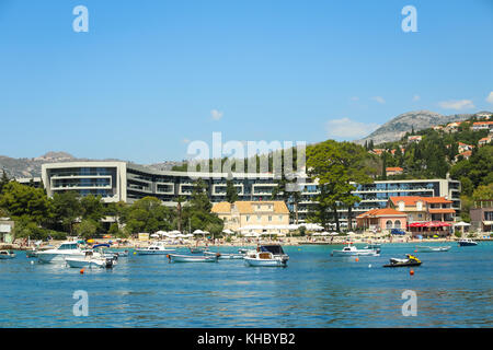 SREBRENO, CROATIA - JULY 18, 2017 : People on the beach in front of Hotel Sheraton with boats anchored in Srebreno, - Stock Photo