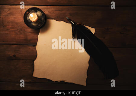old paper and quill pen in candlelight. top view - Stock Photo