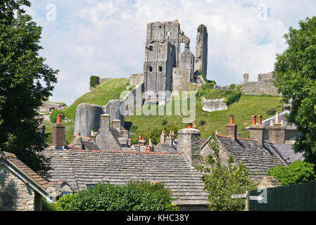 a view across the old stone roof tops of the cottages in the village of Corfe Castle in Devon with the castle ruins - Stock Photo