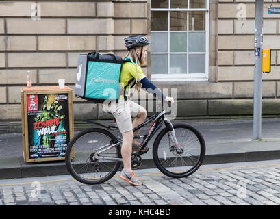 Deliveroo rider on The Royal Mile in Edinburgh, Scotland. UK - Stock Photo