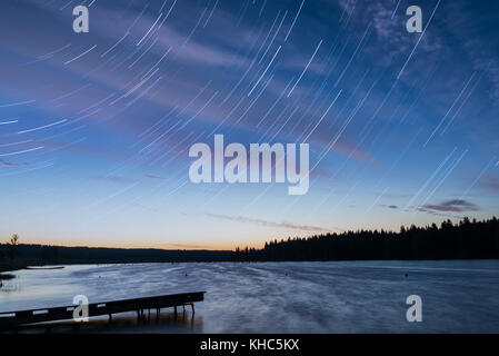 Scenic orange and blue sunset on the lake with falling stars in the form of tracks, shot on a long exposure - Stock Photo