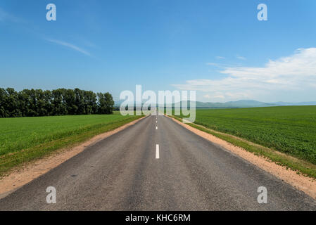 Scenic view from the asphalt road among green fields on the background of mountains and blue sky with clouds - Stock Photo