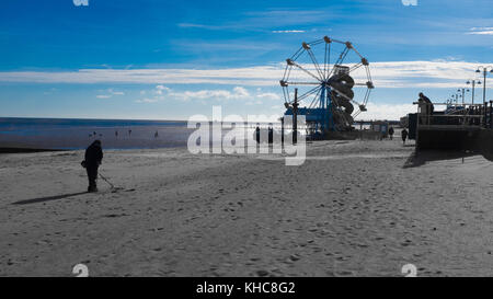 Adult using metal detector on quite beach at cleethorpes near to Ferris Wheel, Helter Skelter and Pier. Seaside - Stock Photo