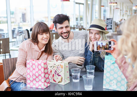 Teenagers as friends can be photographed with the smartphone in the bistro - Stock Photo