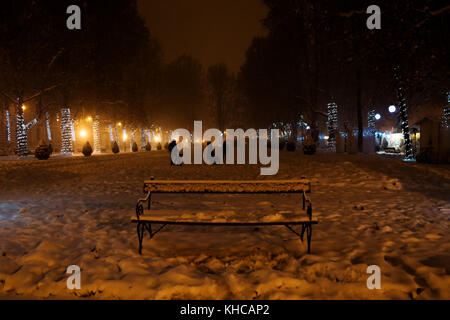 Zagreb, Croatia: January 6 2016: Family playing in the snow during night in light decorated Zrinjevac Park in Zagreb - Stock Photo