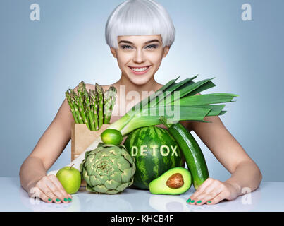 Smiling girl with an abundance of fruits and vegetables. Photo of blonde girl on blue background. Healthy lifestyle - Stock Photo