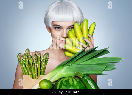 Young girl with an abundance of fruits and vegetables. Photo of smiling blonde girl holding green banana near her - Stock Photo