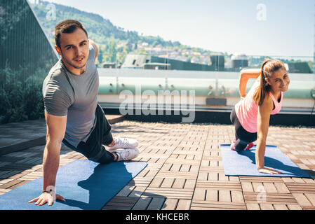 Young couple doing together side plank exercise on the rooftop, outdoors. - Stock Photo