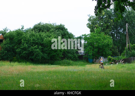 Horizontal photo of beautiful blonde young girl riding her bike in a village - Stock Photo