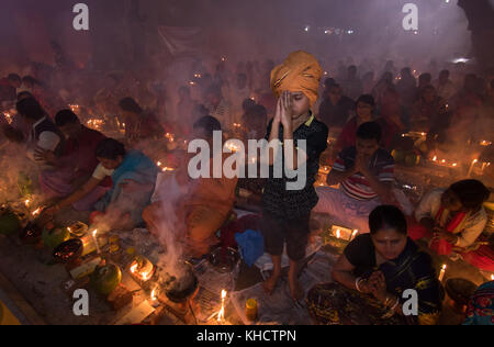 Dhaka, Bangladesh. 14th Nov, 2017. Devotees attend prayer with burning incense and light oil lamps before break - Stock Photo