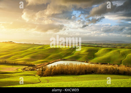 Tuscany misty panorama, lake, rolling hills, fields, meadow and trees at sunset. Italy, Europe - Stock Photo