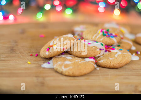 Freshly baked sugar cookies with white icing and rainbow colored sprinkles on wooden board with colored lights in - Stock Photo