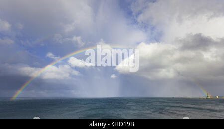 Beautiful double rainbow over ocean water with storm clouds in the sky - Stock Photo