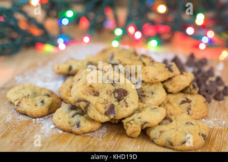 Freshly baked chocolate chip cookies on wooden board with colored lights in background, selective focus - Stock Photo