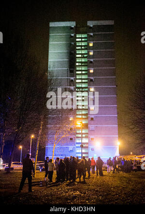 People gather at the scene of a fire at Coolmoyne House in Dunmurry, near Belfast, where residents have been evacuated - Stock Photo