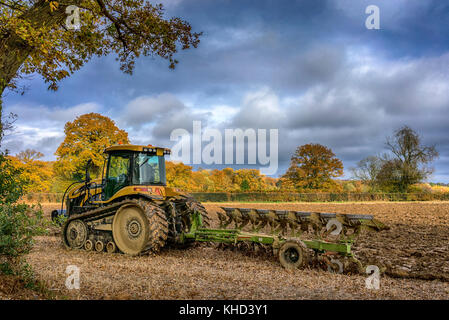 Modern tracked Tractor ploughing field in November in the Chilterns, Buckinghamshire. - Stock Photo