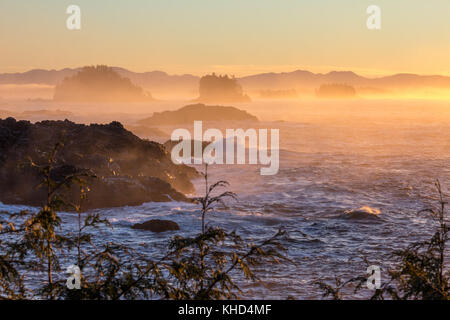Mist from Pacific Ocean waves breaking over rugged islands off-shore from Ucluelet on the wild, west coast of Vancouver - Stock Photo