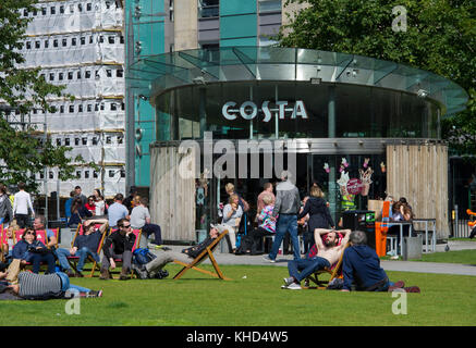 Customers relax in deck chairs outside the Costa coffee shop in St Andrew Square, Edinburgh, Scotland. - Stock Photo