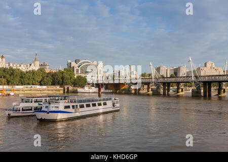 City cruise ships on the river Thames, on background Hungeford Bridge and Golden Jubilee Bridges in the morning, - Stock Photo