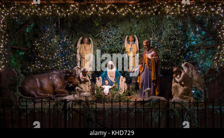 Christmas nativity scene with Mary, Joseph, the Angel Gabriel and animals looking down on baby Jesus in his manger - Stock Photo