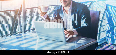 businessman working on computer, drinking coffee and smiling, abstract business banner background with place for - Stock Photo