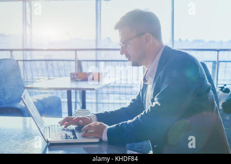 businessman working on computer in modern interior of airport cafe, man using internet on laptop, typing email, - Stock Photo