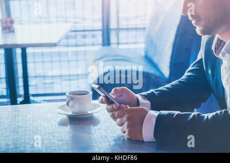 man using mobile phone, close up of hands holding smartphone, online communication on social networks concept - Stock Photo