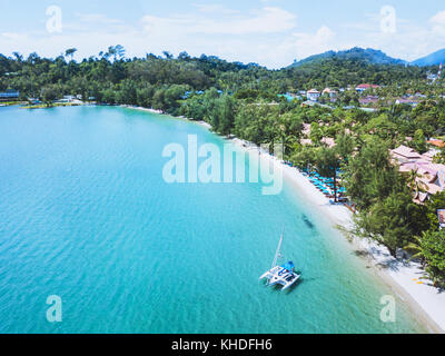 catamaran with sail anchored on beautiful tropical beach of Koh Chang island, Thailand aerial landscape - Stock Photo