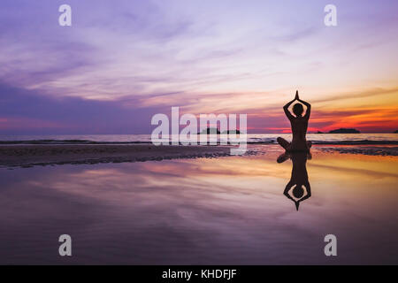 mindful meditation background, silhouette of woman doing yoga on the beach at sunset with reflection - Stock Photo