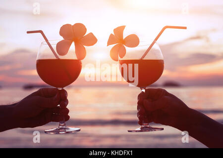 couple drinking cocktails on the beach at sunset, luxury lifestyle - Stock Photo