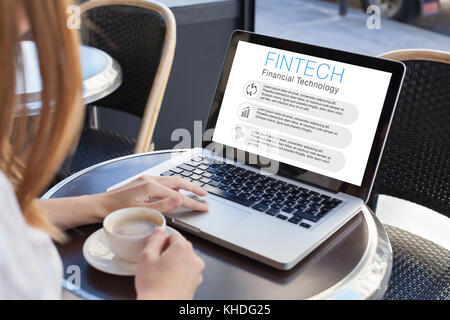 fintech concept, woman reading about financial technology on computer screen - Stock Photo