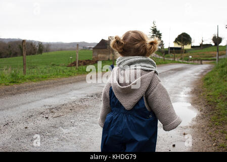 Little girl walking along wet dirt road - Stock Photo
