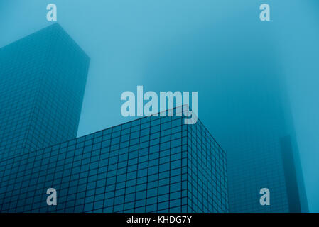Tall skyscrapers disappearing into fog - Stock Photo