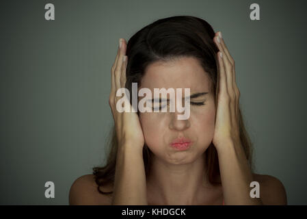 Woman holding hands over ears with eyes closed - Stock Photo