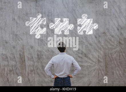 business man looking at the pieces of puzzle, complex solution concept - Stock Photo