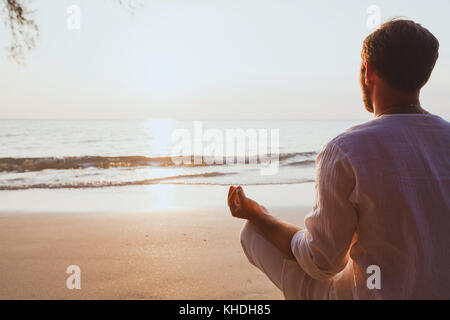meditation, man practicing yoga at sunset beach, background with copy space - Stock Photo