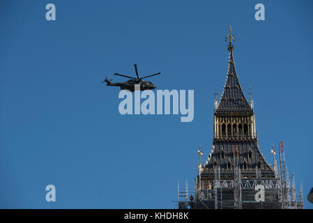 Parliament Square, London, UK. 6th November 2017.  A military helicopter flies past Big Ben in London. - Stock Photo