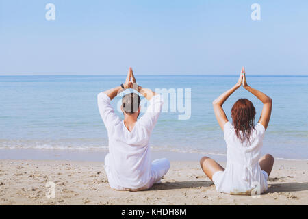 yoga on the beach, two people in white clothes practicing meditation, healthy lifestyle background - Stock Photo
