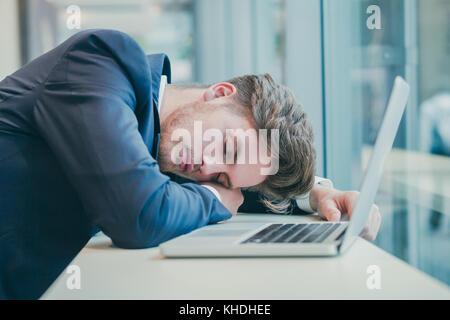 tired businessman sleeping near computer - Stock Photo