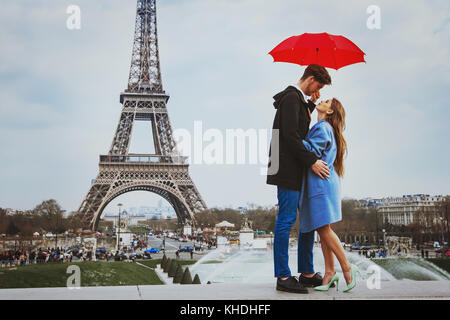 romantic affectionate couple kissing under  umbrella near Eiffel Tower, honeymoon in Paris - Stock Photo