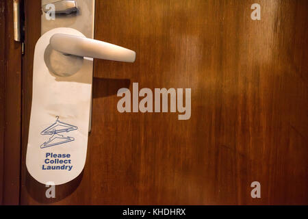 Collect laundry sign on doorknob - Stock Photo