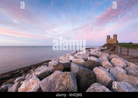 A vivid pink sunset at Reculver Towers, the Medieval church at Reculver on the north Kent coast, UK. The rocks in - Stock Photo