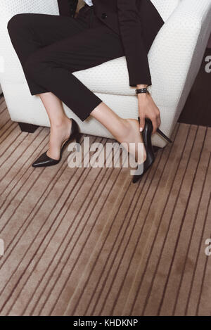 businesswoman with high heeled shoes in hotel room - Stock Photo