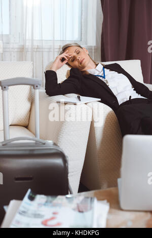 tired businesswoman in hotel room - Stock Photo