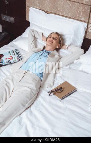 happy businesswoman on bed in hotel - Stock Photo