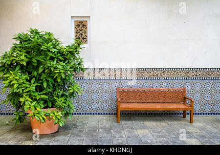 wooden bench with ornaments in front of a wall