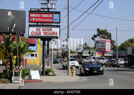 Convertible car and traffic on Melrose Avenue near Cole Ave and Smog Check 24 hour Car Wash sign Hollywood, Los - Stock Photo