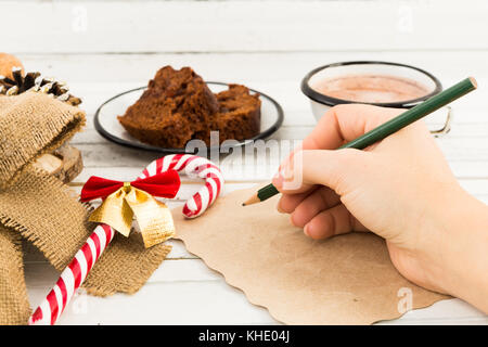 Woman hand writing a letter to Santa Claus on white table with winter holidays decorations, hot cholocate cup and - Stock Photo
