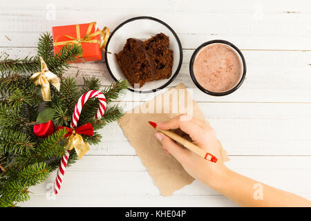 Woman hand writing a Christmas letter on white table with winter holidays decorations - Stock Photo