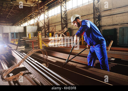 Worker in a white helmet bites the steel wire with wire cutters - Stock Photo